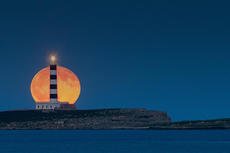 Moonrise behind lighthouse